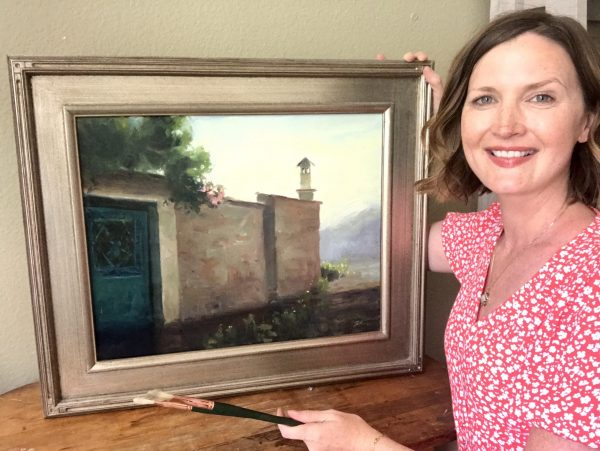 A photo of artist Kelli Folsom holding her original landscape oil painting of pink roses over a village wall with morning light.