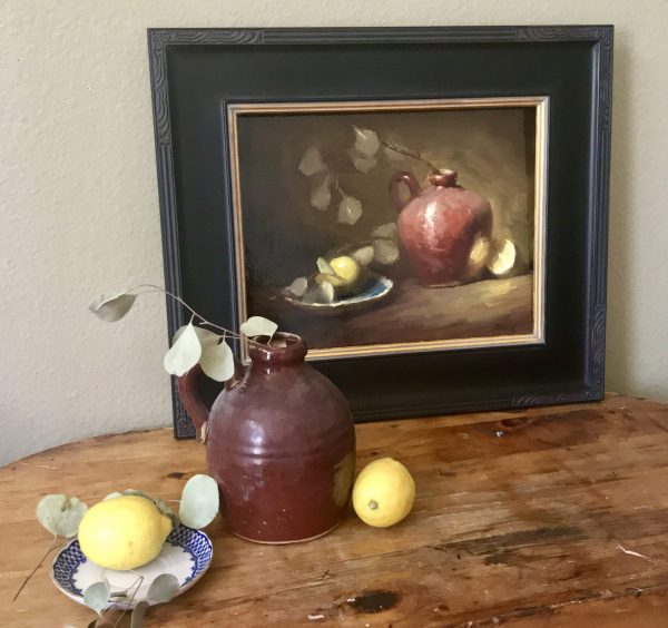 A photo of original kitchen still life painting by artist Kelli Folsom with antique jug and blue and white plate she used to paint the painting.