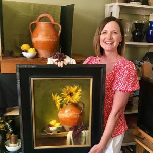 A photo of artist Kelli Folsom holding her original oil painting on panel of a floral still life of sunflowers in confit jar with lemons.