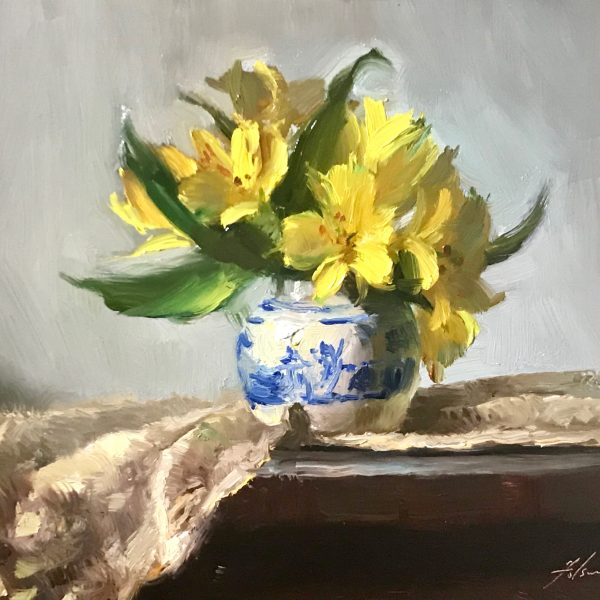 A photo of an original oil painting on panel of a still life painting of yellow lilies, in a blue and white vase and ivory lace.