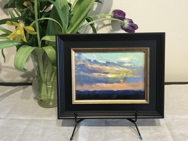 A photo of a framed original oil painting on panel of a landscape painting of a sunrise.